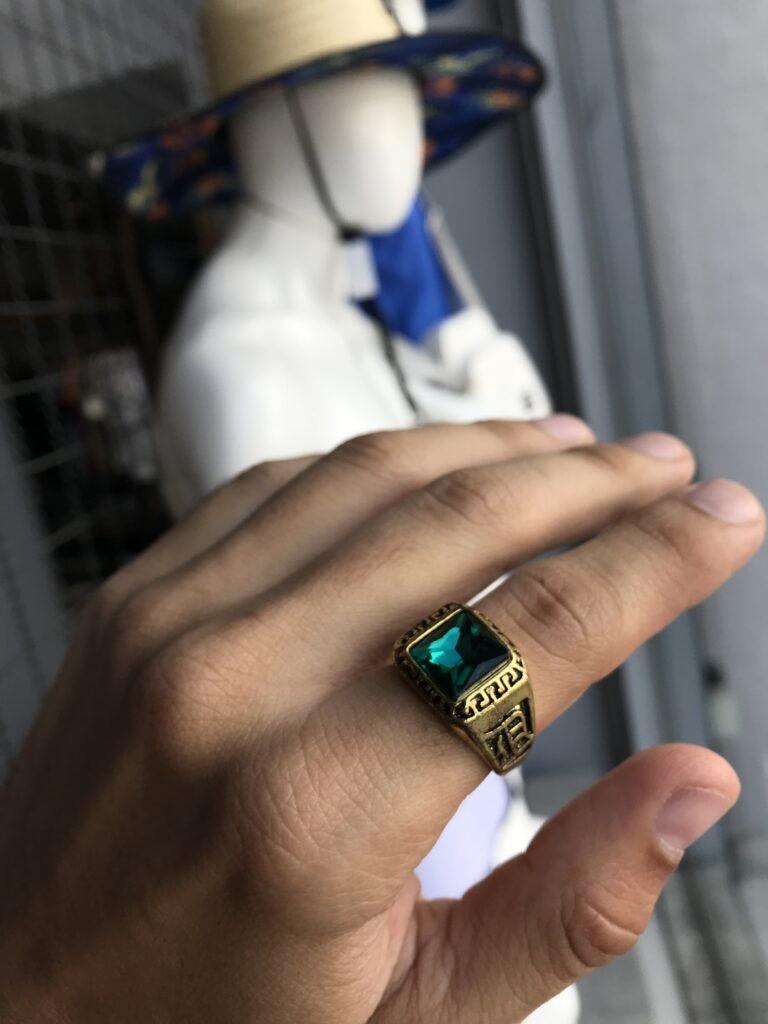 Anel dourado pedra única verde detalhes na lateral aço inoxidável